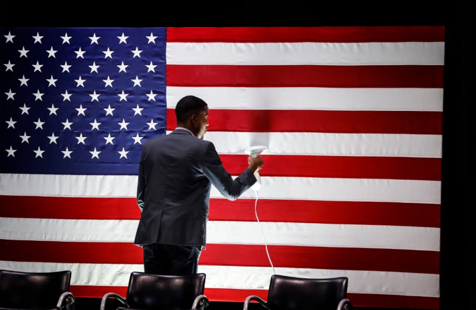 <strong>Kelvin Johnson steams a U.S. flag before Democratic presidential contender Michael Bloomberg's campaign stop at Benjamin L. Hooks Central Library on Thursday, Dec. 19.</strong> (Mark Weber/Daily Memphian)