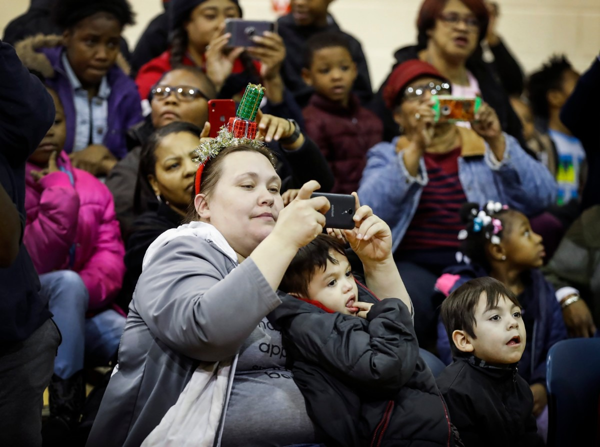 <strong>While holding her son Pablo Perez, 2, Angela Horn (left) takes a picture of the Memphis men's basketball team during a toy giveaway on Dec. 20, 2019, at the Davis Community Center.</strong> (Mark Weber/Daily Memphian)