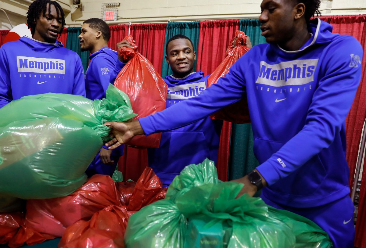 <strong>Alex Lomax (middle) along with his University of Memphis men's basketball teammates handed out gifts during a toy giveaway on Dec. 20, 2019, at the Davis Community Center.</strong> (Mark Weber/Daily Memphian)
