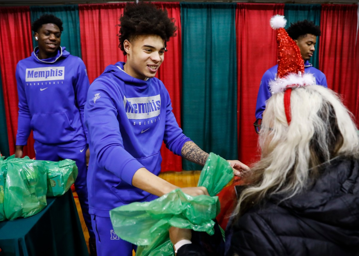 <strong>Lester Quinones (middle) along with his Memphis men's basketball teammates handed out gifts during a toy giveaway on Dec. 20, 2019, at the Davis Community Center.</strong> (Mark Weber/Daily Memphian)