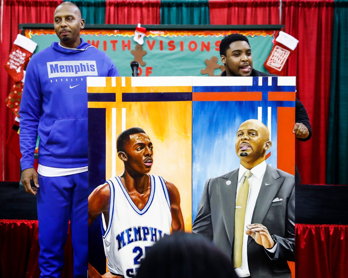 <strong>University of Memphis head basketball coach Penny Hardaway (left) received a painting of himself from local artist Micheal Wilkins (right) during the Tigers' toy giveaway on Dec. 20, 2019, at the Davis Community Center.</strong> (Mark Weber/Daily Memphian)