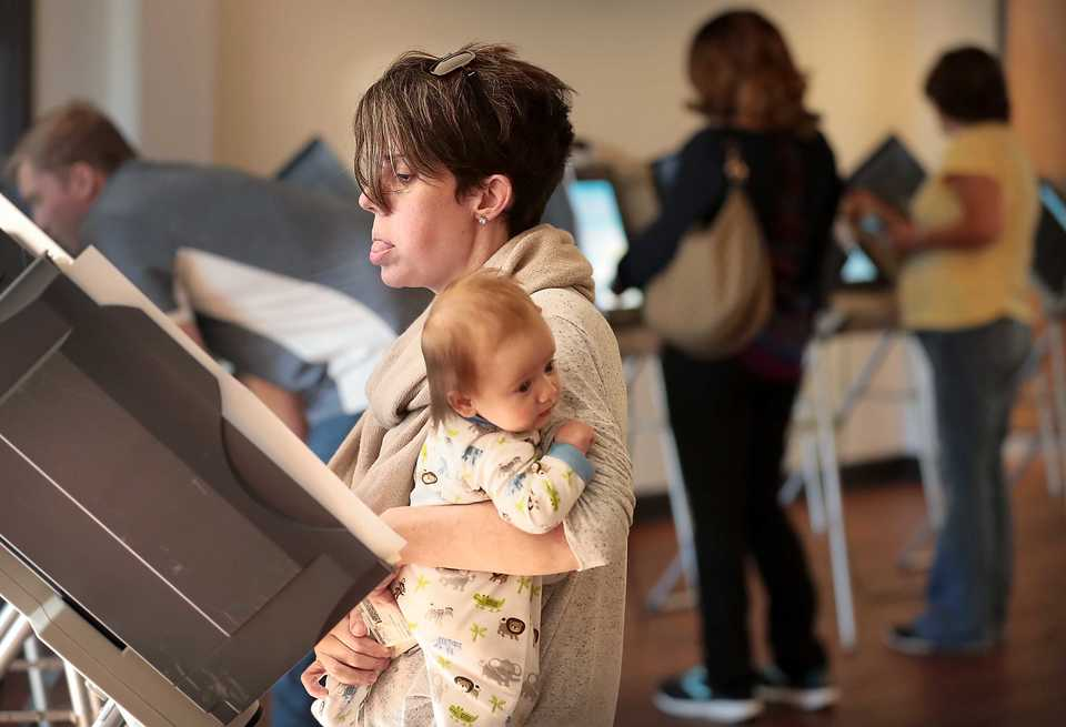 <strong>Lauren Bauler makes calming noises to keep 2-month-old Ella Cate Bauler entertained as she votes at Riveroaks Reformed Presbyterian Church polling location in Germantown on Nov. 6. 2018.</strong> (Jim Weber/Daily Memphian)