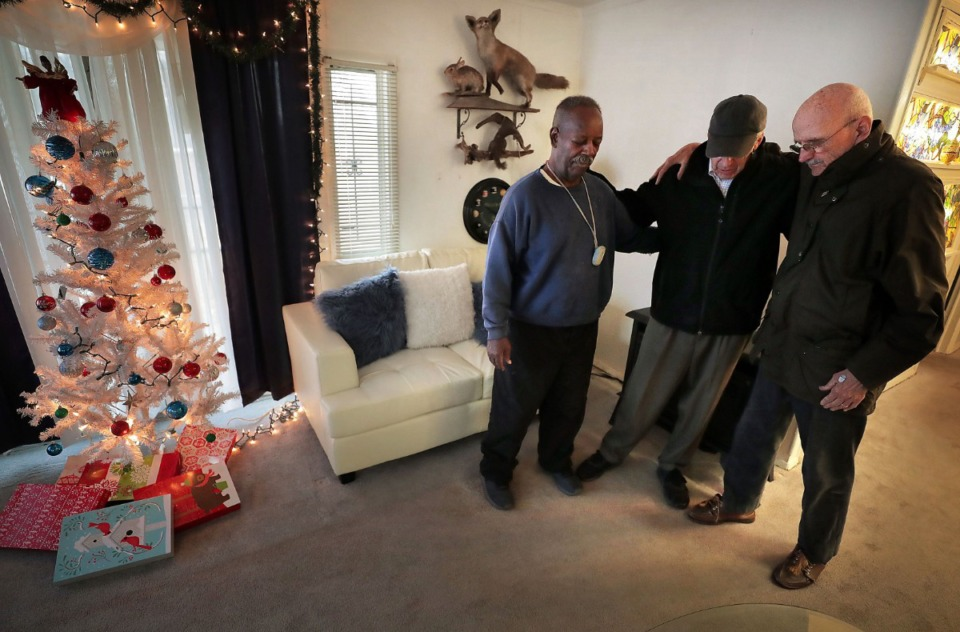<strong>MIFA volunteers Phil Taylor (right) and Bill Craddock pray with friend and client Willie C. (left) after delivering a meal and a Christmas carol on Dec. 10, 2019.&nbsp;</strong> (Jim Weber/Daily Memphian)