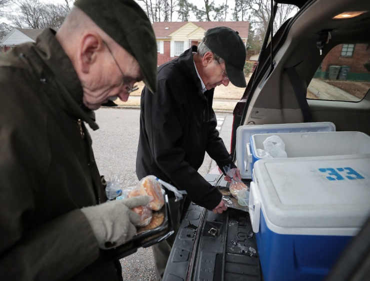 <strong>MIFA driver Bill Craddock (right) and his delivery partner Phil Taylor prepare meals on their Tuesday route in South Memphis on Dec. 10, 2019.</strong> (Jim Weber/Daily Memphian)