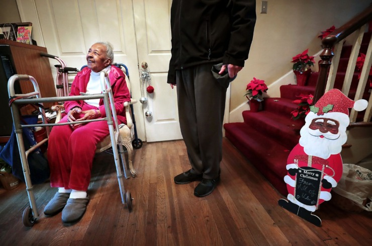"""<strong>Irene M., 98, listens as MIFA volunteer Phil Taylor sings """"Goodnight Irene"""" for her during a visit on Dec. 10, 2019, with Bill Craddock (right) to deliver meals to her home.</strong> (Jim Weber/Daily Memphian)"""