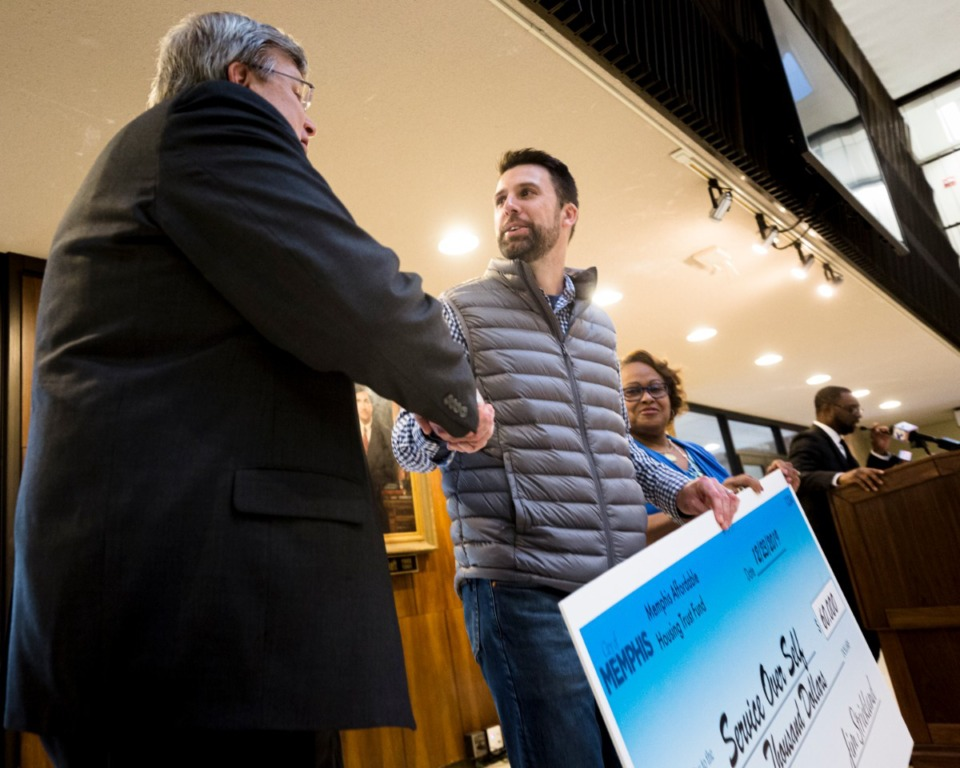 <strong>Mayor Jim Strickland awards Paul Walkley of Service Over Self a grant for $60,000 from the first City Housing Trust at City Hall on Mon., Dec. 23, 2019.</strong> (Ziggy Tucker/Special to the Daily Memphian)