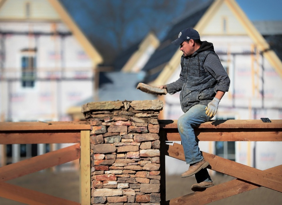 <strong>Aniceto Bolderas puts some finishing touches on a fence column as construction crews frame out homes in a small subdivision on Messick Road in Germantown on Dec. 4, 2019. The housing market forecast for 2020 has been released, projecting that Memphis home sales and prices will be up slightly as the national numbers fall.</strong> (Jim Weber/Daily Memphian)