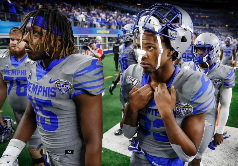 <strong>Dejected University of Memphis teammates Kameron Wilson (left) and Jashon Watkins-Perkins (right) walk off the field after losing to Penn State 53-39 in the Cotton Bowl on Dec. 28, 2019, at AT&amp;T Stadium in Arlington, Texas.</strong> (Mark Weber/Daily Memphian)