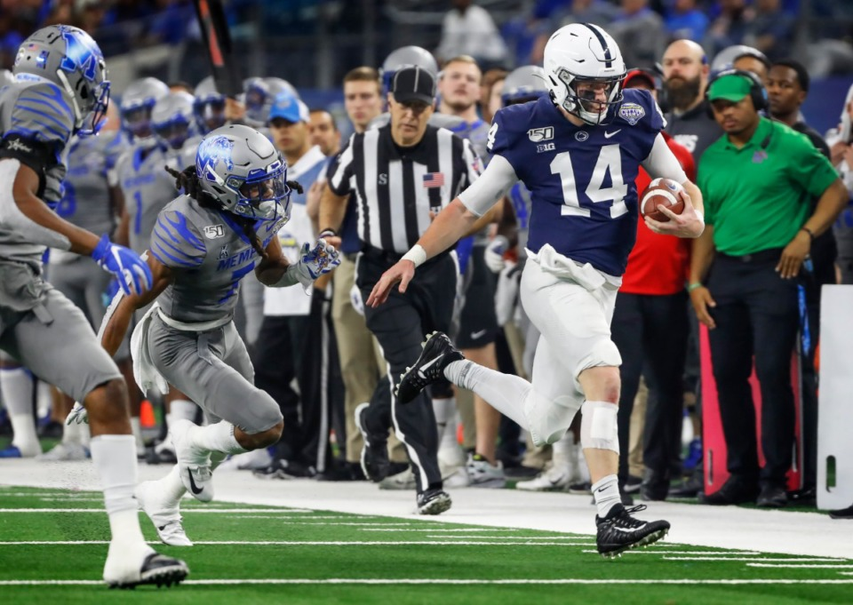 <strong>Penn State quarterback Sean Clifford (right) scrambles past the&nbsp;University of Memphis defense for a first down during action at the Cotton Bowl on Dec. 28, 2019, at AT&amp;T Stadium in Arlington, Texas.</strong> (Mark Weber/Daily Memphian)