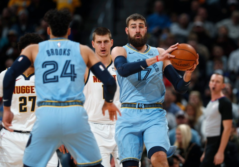 <strong>Memphis Grizzlies center Jonas Valanciunas (center) looks to pass the ball to guard Dillon Brooks (front) as Denver Nuggets center Nikola Jokic defends in the first half of an NBA game on Dec. 28, 2019, in Denver.</strong> (AP Photo/David Zalubowski)