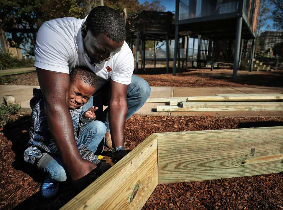 "<strong>Downtown Elementary kindergarten student Kaleb Hale, 5, winces as Octavius Nickson shows him how to use a power drill for the first time while building his school's ""nest"" at River Garden which officially opens on Nov. 9, 2018. Shelby County Schools students designed and helped build several life-sized nests to be included in the park.</strong> (Jim Weber/Daily Memphian)"
