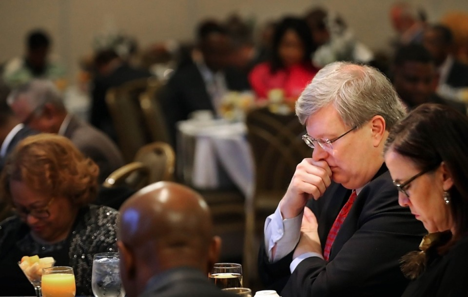 <strong>Mayor Jim Strickland and his wife, Melanie Strickland, (right) listen to a blessing of the meal by Rev. Jessica Morris during the mayor's annual New Year's Eve Prayer Breakfast on Dec. 31, 2019, at the University of Memphis Holiday Inn. Local civic leaders, pastors and politicians were on hand to usher in the new year with prayers from Memphis clergy.</strong> (Jim Weber/Daily Memphian)