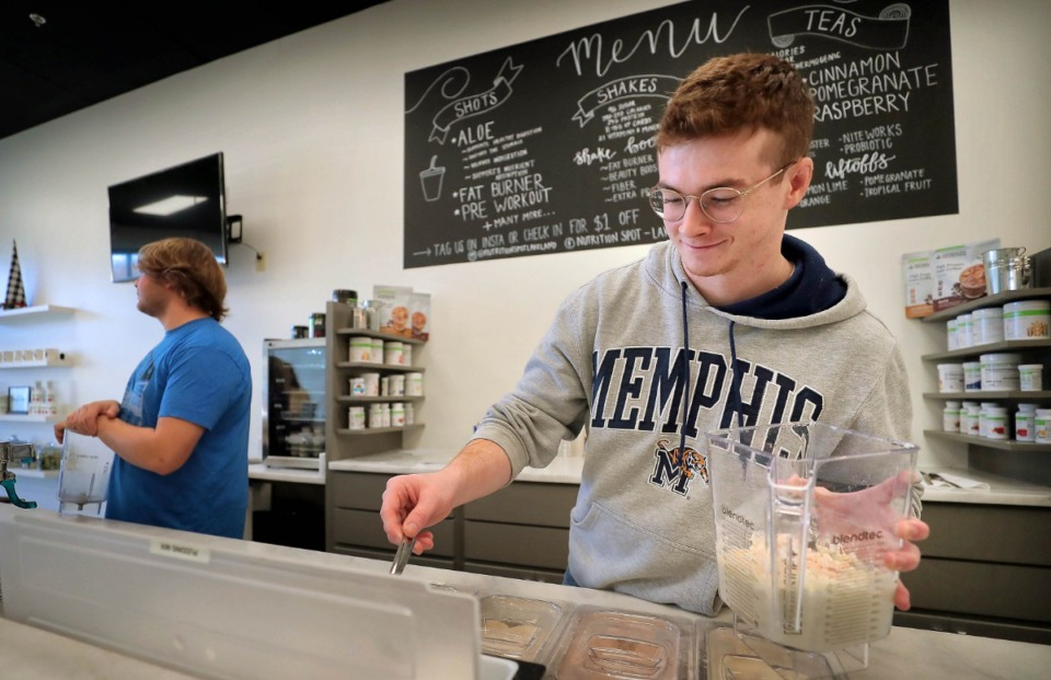 <strong>Justin Donahue mixes up a Blueberry Muffin sports shake at the Nutrition Spot, a new health shake and juice bar at U.S. Highway 64 and Canada Road in Lakeland. Co-owners Shanda Bearden and Amy Foster have found a sweet spot for their business, with close proximity to several suburban gyms.</strong> (Jim Weber/Daily Memphian)