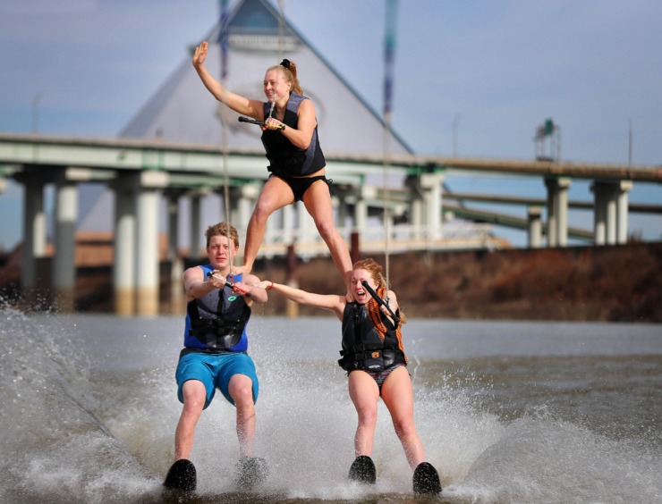 <strong>Ashley Piskorski waves to the dock from her perch on the shoulders of siblings Cole (left) and Kayla Piskorski during the 43rd annual Ski Freeze at the Mud Island River Park on Jan. 1, 2020. Hosted by the Collierville Ski Club, water skiers, barefooters and wakeboarders braved the frigid water of the Wolf River to raise money for The Dream Factory of Memphis which grants wishes for critically and chronically ill children ages 3 through 18.</strong> (Jim Weber/Daily Memphian)