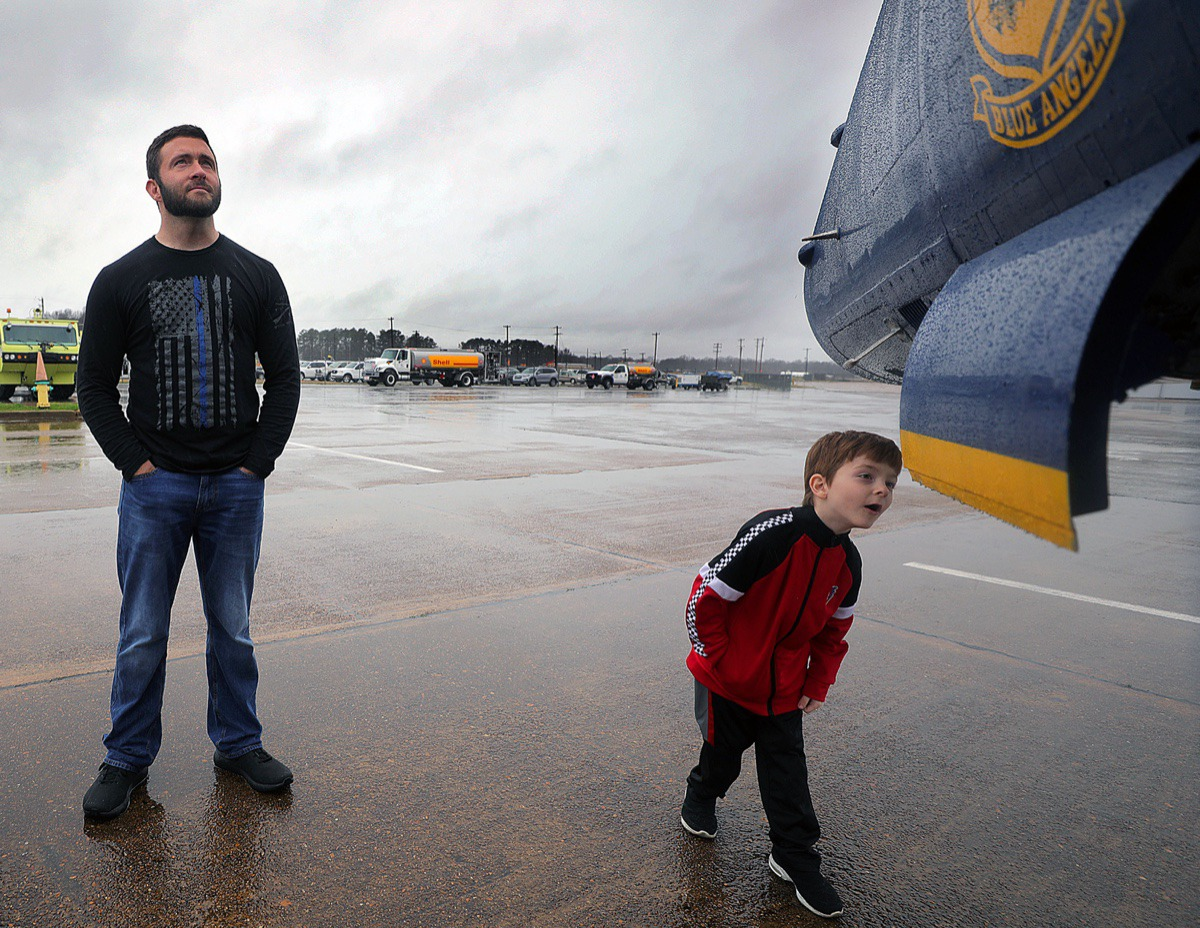 <strong>Connor Van Horn curiously inspects the nose of the Blue Angels jet parked at the Millington-Memphis Airport Jan. 2, 2020, while Alex Van Horn looks on. The Van Horns were one of several families who braved the rain for a sneak peak at the U.S. Navy fighter jet that will be at the Mid-South Airshow later this year.</strong> (Patrick Lantrip/Daily Memphian)