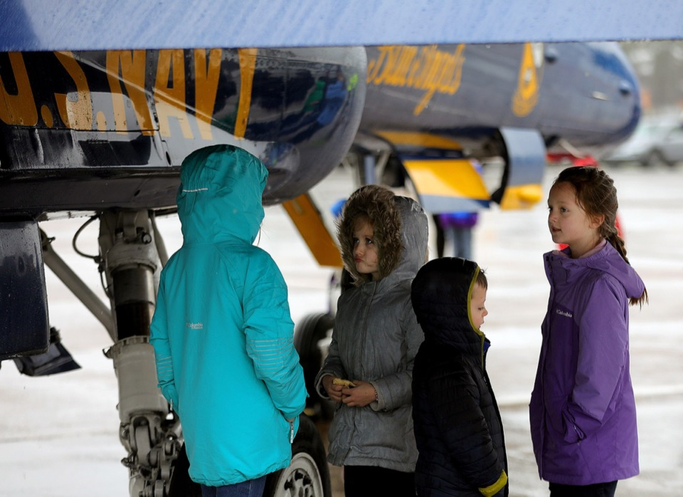 <strong>Adalyn Ferrell (from left), Aubrey Garrett, Carter Garrett and Vivian Ferrell take shelter under the wing of a Blue Angels jet that was at the Millington-Memphis Airport Jan. 2, 2020, promoting the Mid-South Airshow.</strong> (Patrick Lantrip/Daily Memphian)
