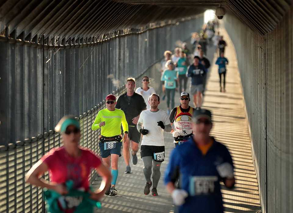<strong>Runners in the second annual Big River Crossing Half Marathon descend from the bridge into Arkansas on Nov. 3, 2018 to run the newly-paved 7 mile loop of trails in West Memphis.</strong> (Jim Weber/Daily Memphian)