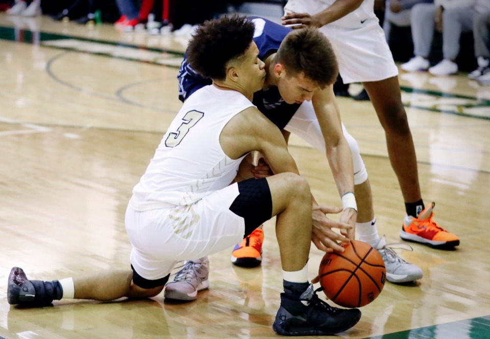 <strong>Arlington defender Philip Dotson (front) battles Hamilton Heights forward Samson Ruzhentsev (back) for a loose ball during action Friday, Jan. 3, 2020, at Hoopfest.</strong> (Mark Weber/Daily Memphian)
