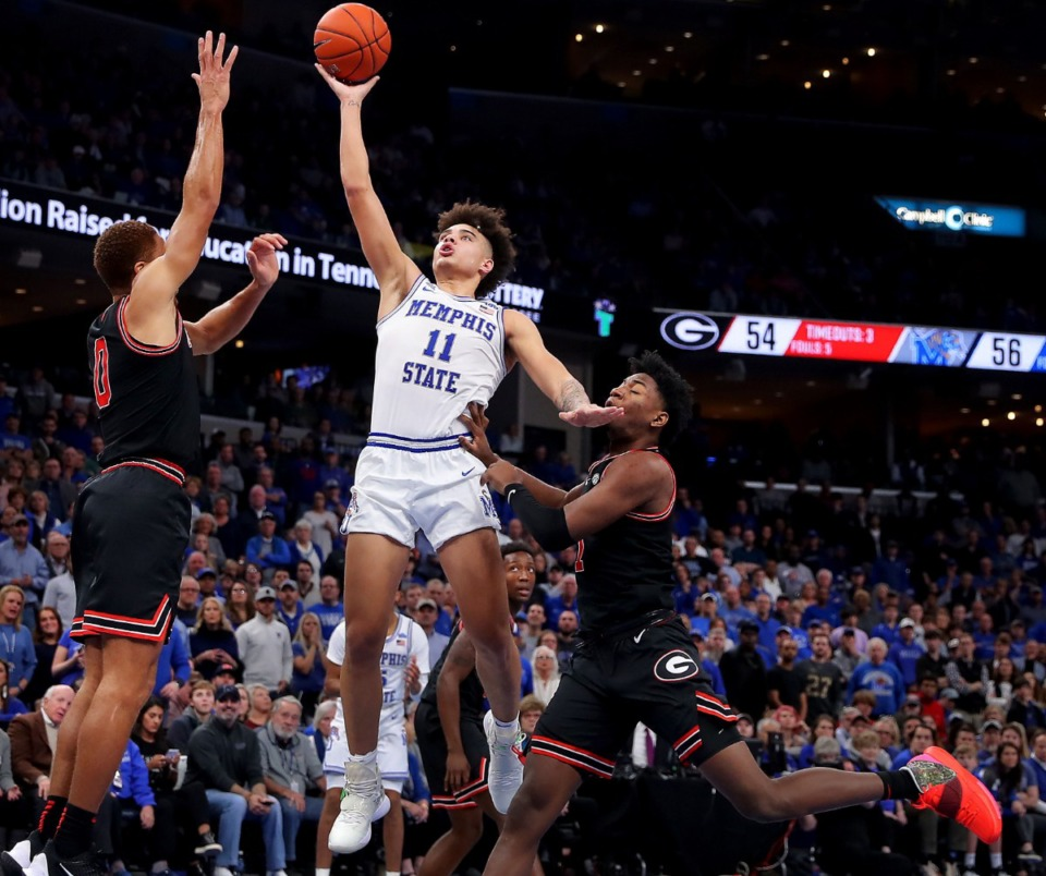 <strong>University of Memphis guard Lester Quinones (11) shoots under pressure by the Bulldogs' Donnell Gresham Jr. (0) and Jaykwon Walker during the Tigers' game on Jan. 4, 2020, against Georgia at the FedExForum.</strong> (Jim Weber/Daily Memphian)