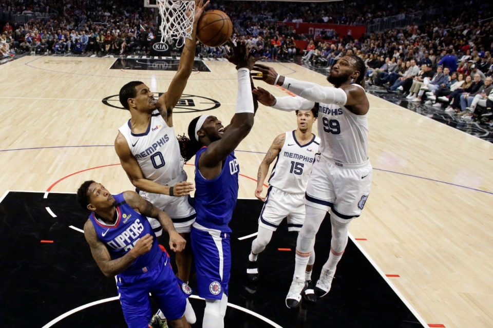 <strong>Los Angeles Clippers' Montrezl Harrell (center) tries to grab a rebound between Memphis Grizzlies' De'Anthony Melton (0) and Jae Crowder (99) during the second half of a game on Jan. 4, 2020, in Los Angeles.</strong> (AP Photo/Marcio Jose Sanchez)
