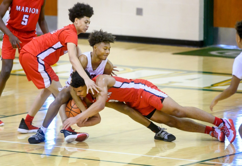 <strong>Marion High School's Detrick Reeves Jr. fights for a loose ball against East High School's Tadarius Jacobs with Marion's Timothy McDonald reaching from behind during their Hoopfest contest on Jan. 4, 2020 at Briarcrest High School.</strong> (Greg Campbell/Special to The Daily Memphian)