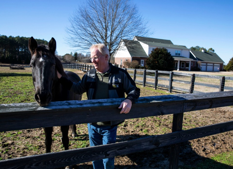 <strong>Robert Slaughter enjoys a warm winter day with one of his horses at his home on Quinn Road in southeast Shelby County on Sunday, Jan. 5. Slaughter and his neighbors are concerned that a proposed development of more than 500 houses on land adjacent to Slaughter's property will ruin the rural, farm-like feel of their homes.</strong> (Mike Kerr/Special to Daily Memphian)