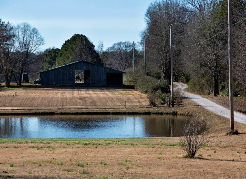 <strong>A long gravel driveway passes a neighbor's barn leading to Robert Slaughter's rural home, which features a pond and a horse barn, off Quinn Road in southeast Shelby County.</strong> (Mike Kerr/Special to the Daily Memphian)