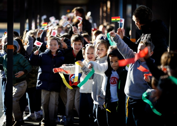 <strong>St. Francis of Assisi Catholic School students wave Memphis in May and Ghana flags as a CN Railway train delivered a MIM World Cargo Crate from Ghana Tuesday, Jan. 7, 2020, to the Cordova campus.</strong> (Mark Weber/Daily Memphian)