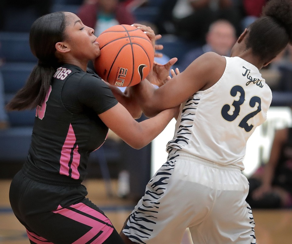 <strong>Lady Mustangs guard (let) Brittani Wells battles for a loose ball with the Tigers' Charmen Taylor (32) during Houston High School's girls basketball game against Arlington on Jan. 7, 2020, at Arlington High School.</strong> (Jim Weber/Daily Memphian)