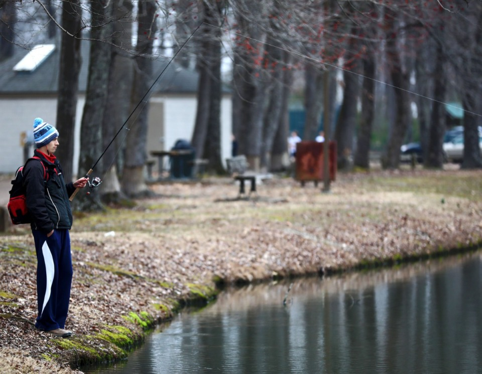 <strong>Joshua Lerma fishes in a small pond in Houston Levee Park behind Houston High School on Feb. 28, 2019. Germantown Municipal School District will get most of Houston Levee Park in exchange for land at the new Forest Hill Elementary School where a second city water tower is planned. </strong>(Daily Memphian file)