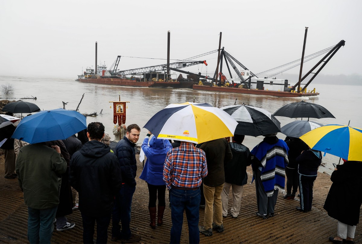 <strong>In heavy fog and a misting rain, a barge rolls up the Mississippi River as a crowd gathers for St. John Orthodox Church's Blessing of the River event on Saturday, Jan. 11, 2020, after severe storms rolled through the Memphis area Saturday morning.</strong> (Mark Weber/Daily Memphian)