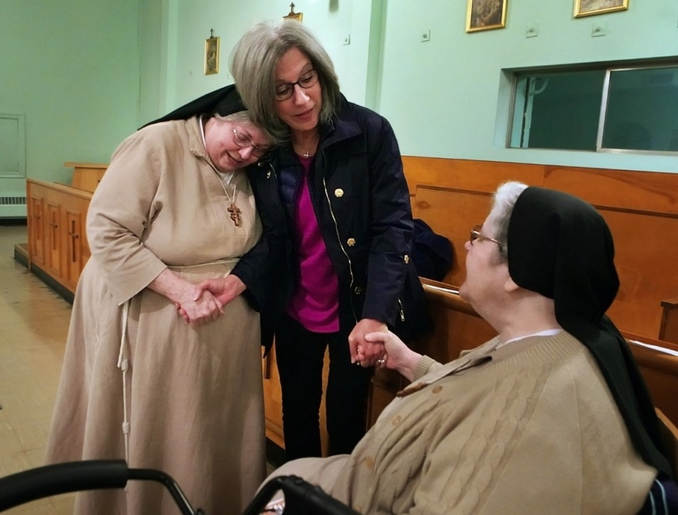 <strong>Friend of the monastery Kathleen Laakso (center) bids one of the many tearful goodbyes in the nuns' last days at the monastery. Sister Claudia (left) lived at the monastery for over 50 years, along with Sister Mary Marguerite (right).</strong> (Karen Pulfer Focht/Special to The Daily Memphian)