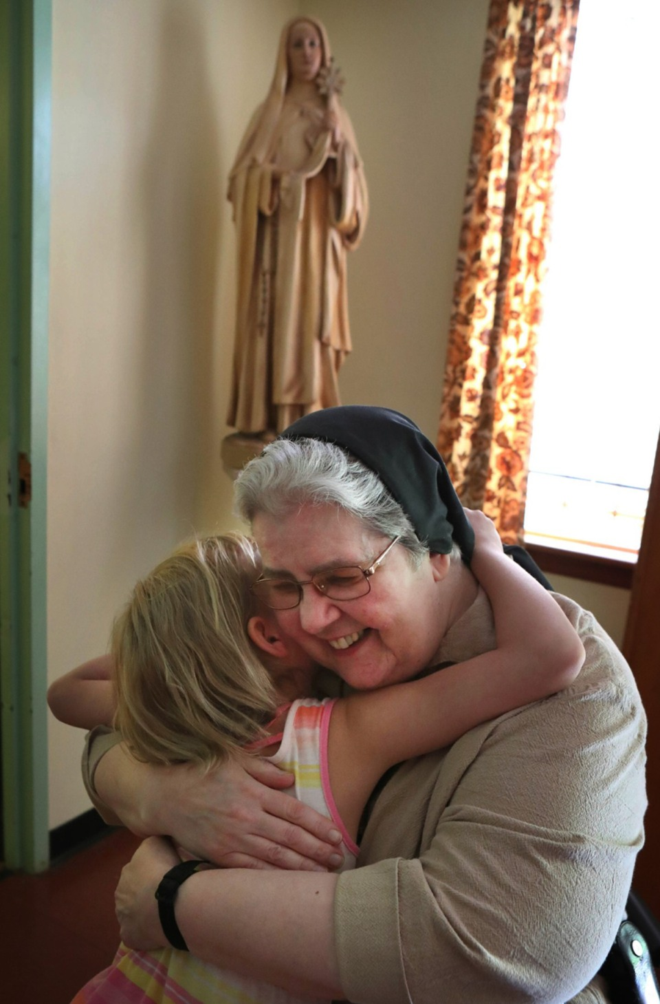 <strong>A child hugs Sister Mary Marguerite following the last public mass for the Feast of St. Clare on Aug, 11 2019, at the Monastery of St. Clare in Memphis. The nuns have since left the building that housed their order since 1932 in the Frayser neighborhood. The monastery closed at the end of 2019.</strong> (Karen Pulfer Focht/Special to The Daily Memphian)