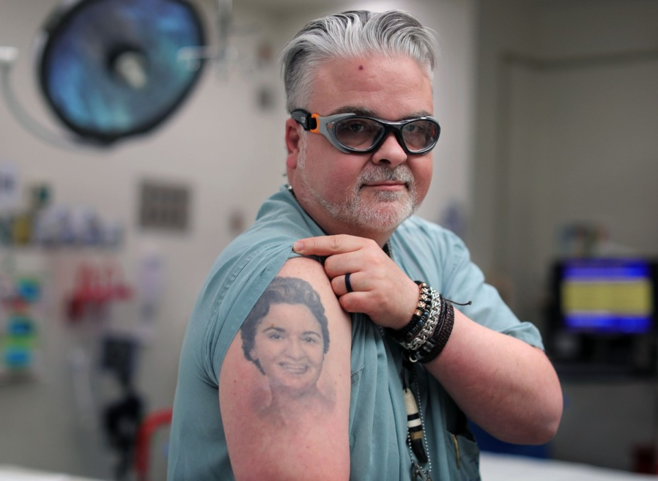 <strong>Dr. Lou Magnotti,&nbsp;in an operating room at Regional One, shows off a tattoo of his mother on Monday, Jan. 13. Adorned in necklaces, chains and even a bear claw, Magnotti may not look like your typical surgeon, but his appearance actually helps some patients feel more comfortable, he said.</strong> (Patrick Lantrip/Daily Memphian)