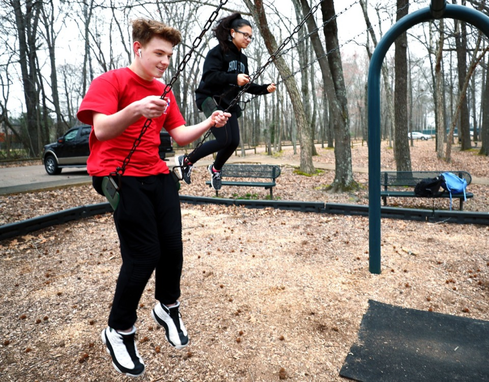 <strong>Jackson Bennetz (left) and Mari-Ann Becerra (right), both freshmen at Houston High School, swing in the Houston Levee Park after school.</strong>&nbsp;<strong>The school district will gain space for athletic fields in the park under the land swap Germantown aldermen approved Jan. 13.&nbsp;The swap has to be approved by the Board of Education next.</strong> (Houston Cofield/Daily Memphian)