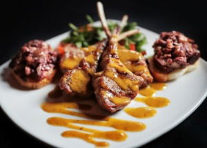 <strong>Grilled lamb lollipops are glazed with rosemary sauce with olive and tomato tapenade on a baguette at Tommy Peters' new Moondance Grill restaurant, which opened last year in Thornwood on Germantown Parkway.</strong> (Jim Weber/Daily Memphian)