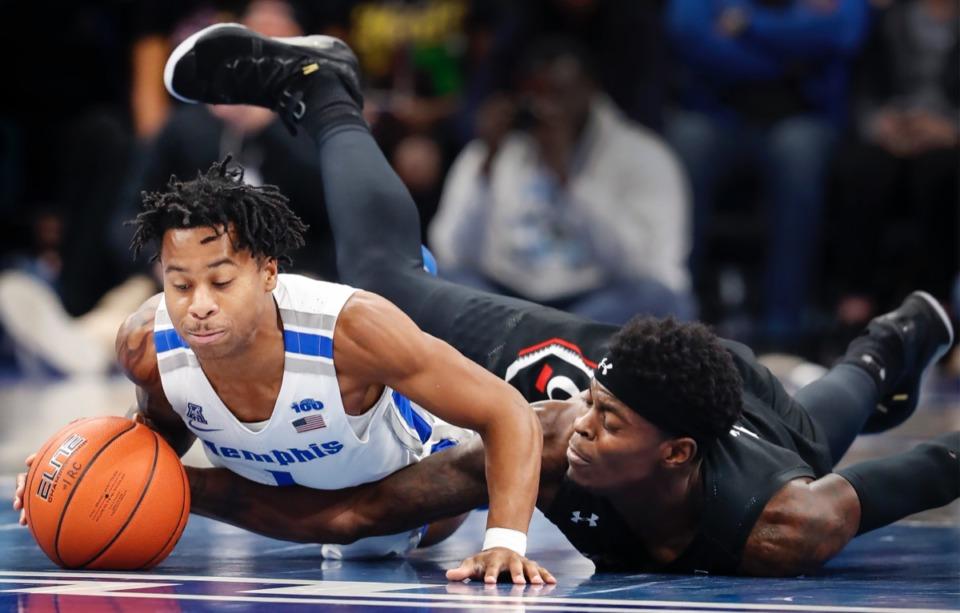 <strong>Memphis defender Tyler Harris (left) and Cincinnati forward Tre Scott (right) end up on the floor Thursday, Jan. 16, 2020, at FedExForum, in pursuit of a loose ball.</strong> (Mark Weber/Daily Memphian)