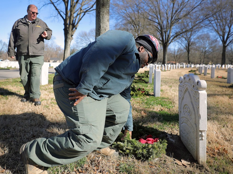 <strong>Howard Hurst fixes a wreath recently laid on the grave of&nbsp;</strong><span><strong>Capt. Nathaniel Reed, a Newburyport, Massachusetts, native who fought for the Union during the Civil War and died from disease or a severe arm injury.</strong>&nbsp;</span>(Patrick Lantrip/Daily Memphian)