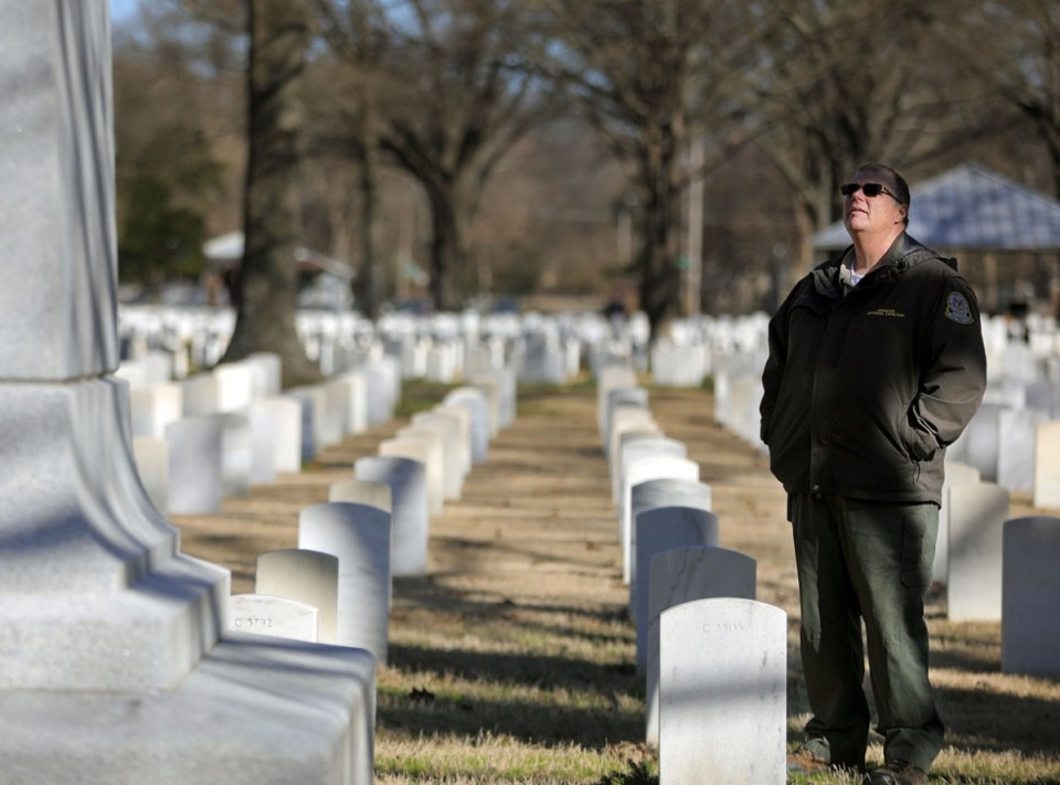 <strong>Randall Crow, cemetery foreman at Memphis National Cemetery, looks up at a monument that was donated by the state of Minnesota to honor its fallen sons who died in Tennessee during the Civil War and were subsequently buried in the cemetery.</strong> (Patrick Lantrip/Daily Memphian)
