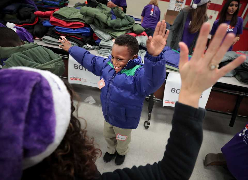 <strong>Hawkins Mill Elementary student Jermarcus Robinson stretches out to see how his new coat fits on Thursday, Nov. 8. Memphis-based FedEx and the national nonprofit Operation Warm distributed more than 700 winter coats this week at Hawkins Mill and Hamilton elementary schools. </strong>(Jim Weber/Daily Memphian)