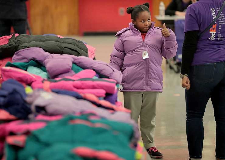 <strong>Aniya Reedos gives her approval for a new coat she received from Philadephia-based Operation Warm, which distributes winter coats to children at schools around the country. About 130 employees of FedEx showed up over two days to assist in the coat giveway.</strong> (Jim Weber/Daily Memphian)
