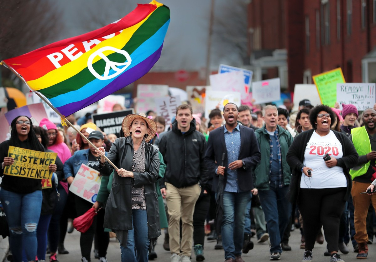 <strong>Peace flag in hand, Patty Crawford (left) leads the Memphis Women's March Downtown on Jan. 18, 2020, as over 250 women's rights advocates gathered in the shadow of a looming election year to build awareness for equality, reproductive rights and discrimination issues.</strong> (Jim Weber/Daily Memphian)