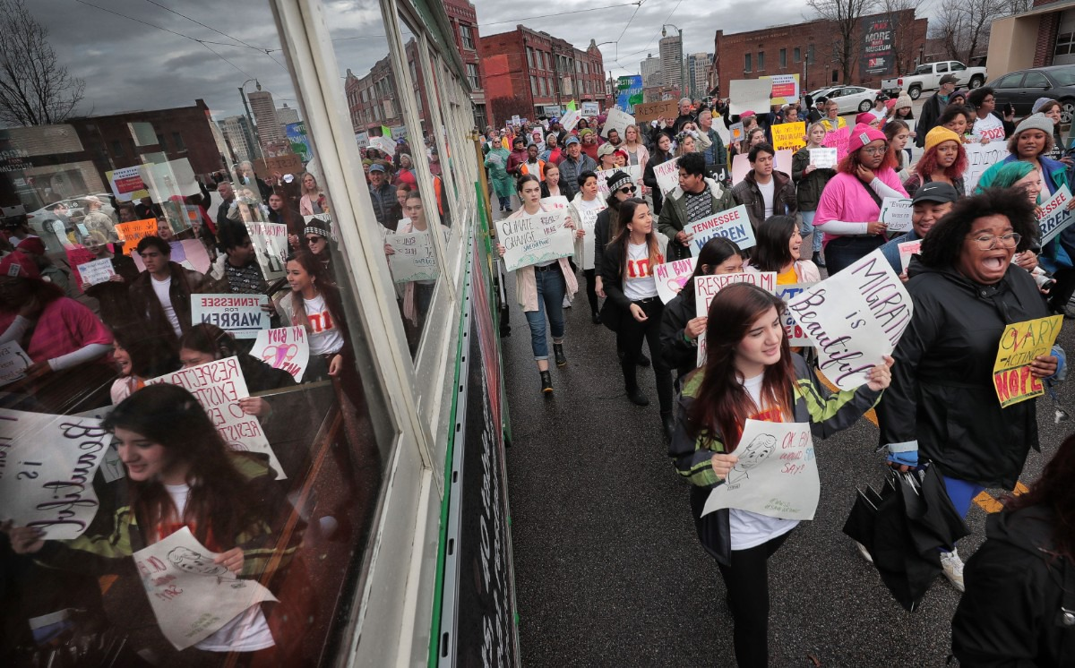 <strong>Marchers pass a trolley on South Main during the Memphis Women's March Downtown on Jan. 18, 2020, as over 250 women's rights advocates gathered in the shadow of a looming election year to build awareness for equality, reproductive rights and discrimination issues.</strong> (Jim Weber/Daily Memphian)