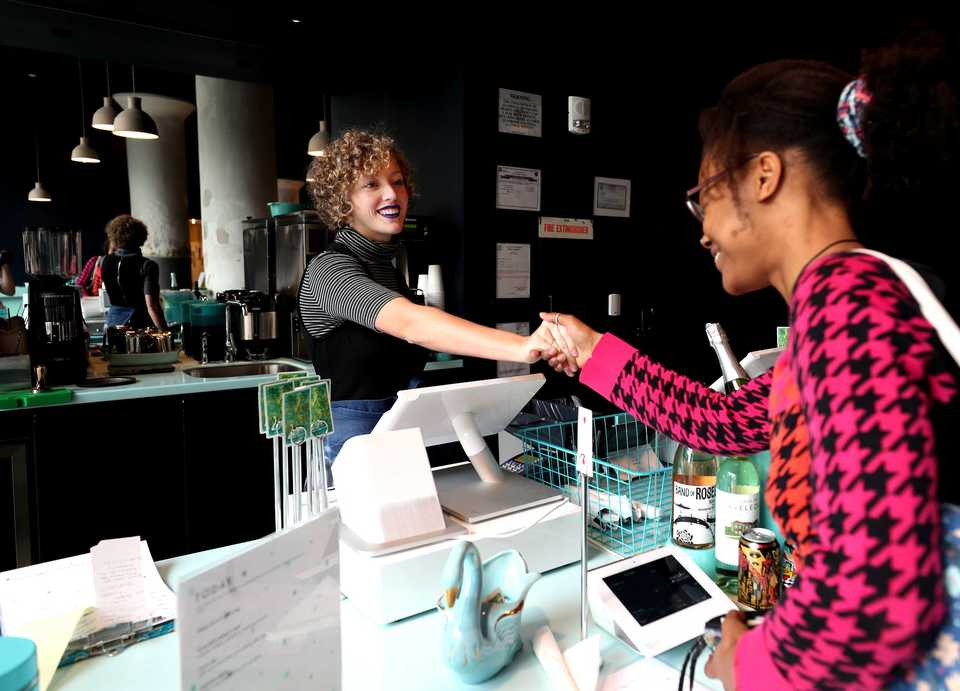 <strong>Olivia Cantrall (left) an employee at Today &amp; Always, a cafe inside Crosstown Arts, serves a customer at the bar. Crosstown Concourse has more than eight restaurants, bars and cafes offering a variety of food and drink choices.</strong> (Houston Cofield/Daily Memphian).