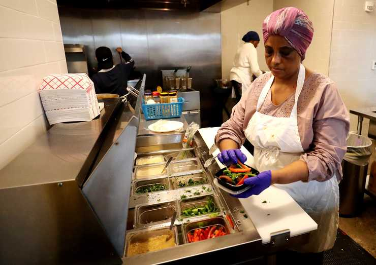 <strong>Ibtisam Salih, a chef at Global Cafe inside Crosstown Concourse, puts some chopped bell peppers on an African dish before serving a customer.</strong> (Houston Cofield/Daily Memphian)