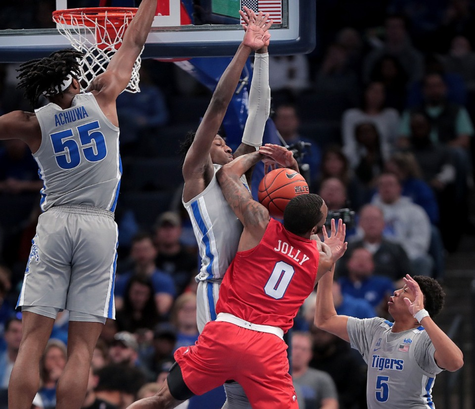 <strong>University of Memphis guard Damion Baugh (center) fouls the Mustangs' Tyson Jolly (0) while trying to block a shot during the Tigers' game on Jan. 25, 2020, against SMU at the FedExForum.</strong> (Jim Weber/Daily Memphian)