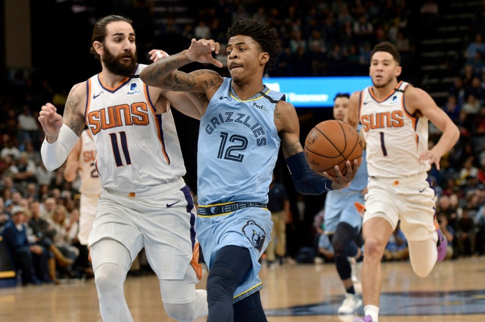 <strong>Memphis Grizzlies guard Ja Morant (12) drives ahead of Phoenix Suns guards Ricky Rubio (11) and Devin Booker (1) in the first half of an NBA basketball game Sunday, Jan. 26, 2020, at FedExForum.</strong> (Brandon Dill/AP)
