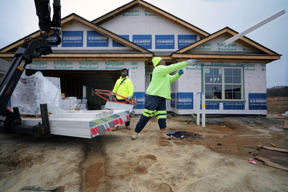 <strong>Frank Davis (center), with Rew Materials, tosses a discarded piece of sheetrock in the trash while coworker James Morgan looks on. The &nbsp;two were dropping off supplies to a jobsite in the Ruby Estates subdivision in Whitehaven Jan. 17, 2020.</strong> (Patrick Lantrip/Daily Memphian)
