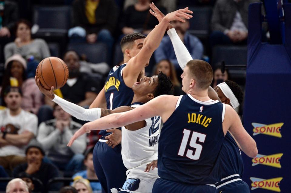 <strong>Memphis Grizzlies guard Ja Morant (12) shoots between Denver Nuggets center Nikola Jokic (15) and forward Michael Porter Jr. (1) Jan. 28, 2020, at FedExForum.</strong> (Brandon Dill/AP)