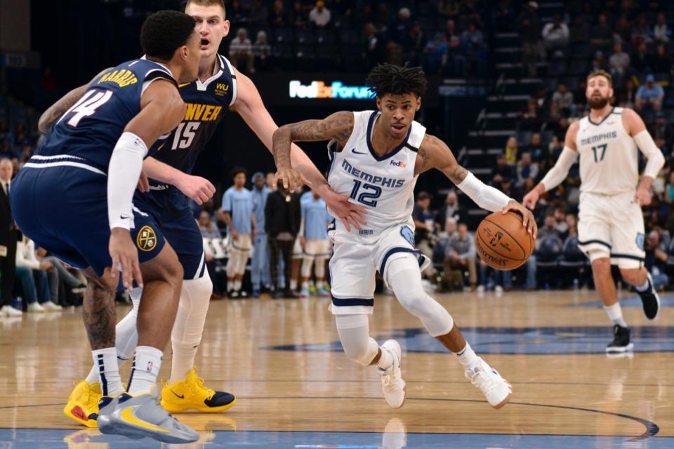 <strong>Memphis Grizzlies guard Ja Morant (12) drives to the basket against Denver Nuggets center Nikola Jokic (15) and guard Gary Harris (14) Jan. 28, 2020, at FedExForum.</strong> (Brandon Dill/AP)
